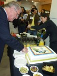 Adrian Bullock cutting the cake featuring his book 'Book Production'.