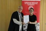 Yanhong Zhou receiving certificate from Adrian Bullock